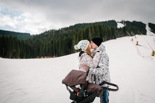 Um jovem casal se beijando perto de um carrinho de bebê na neve nas montanhas