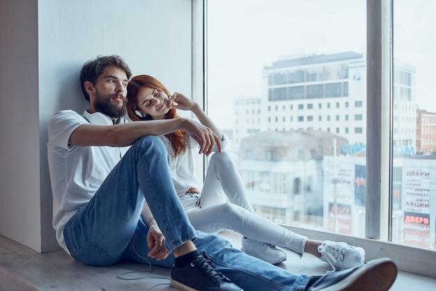 Um jovem casal senta-se perto da janela com fones de ouvido juntos apartamentos. foto de alta qualidade