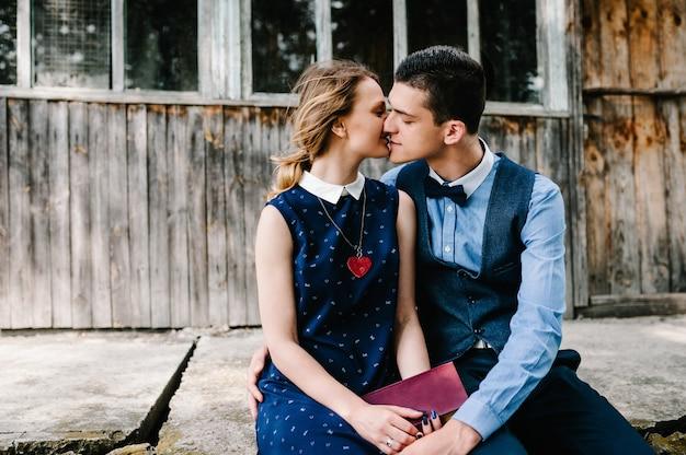 Um jovem casal sentado, beijando e abraçando segura um livro fechado nas mãos perto de uma casa velha de madeira com janelas. fechar-se.