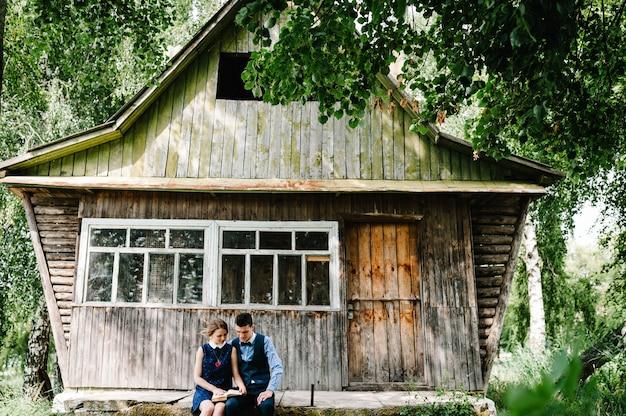 Um jovem casal sentado e se abraçando, lendo um livro aberto perto de uma velha casa de madeira com janelas na floresta entre as árvores