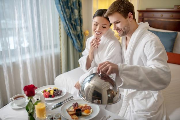 Um jovem casal tomando café da manhã no quarto do hotel