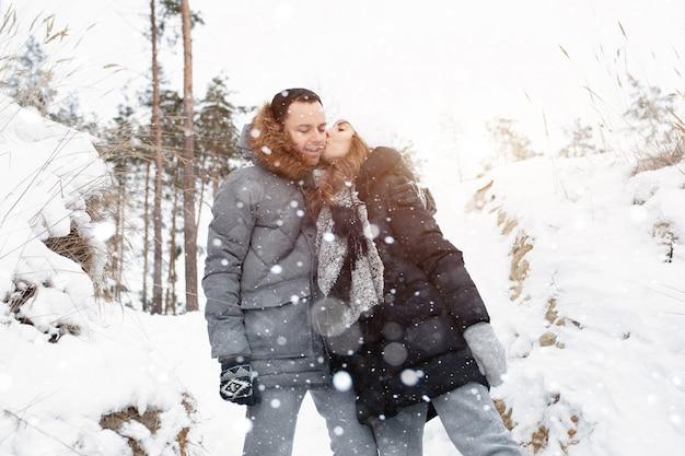 Um jovem casal, um homem e uma mulher estão andando em uma floresta coberta de neve do inverno.