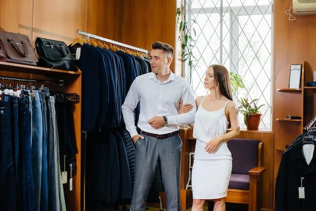 Um jovem casal vai às compras e pega um terno masculino.