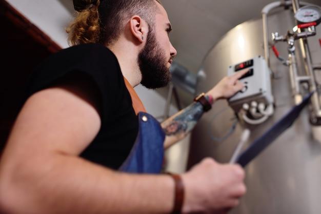 Um jovem cervejeiro atraente com uma barba examina o equipamento para fabricação de cerveja e registra os resultados no papel.