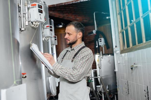 Um jovem cervejeiro barbudo monitora as leituras do sensor durante o processo de fermentação. fazendo cerveja.