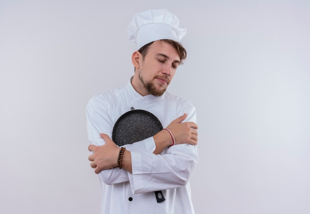 Um jovem chef barbudo calmo de uniforme branco abraçando a frigideira com os olhos fechados em uma parede branca