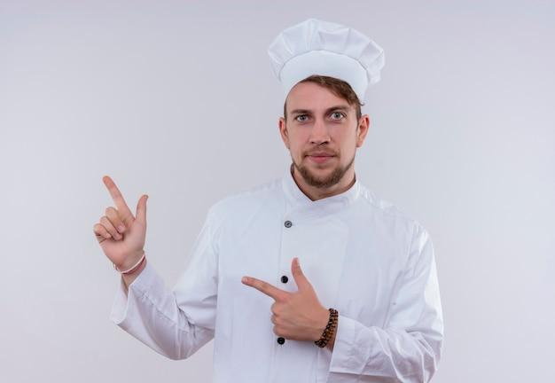 Um jovem chef barbudo confiante vestindo uniforme branco de fogão e chapéu apontando para cima com o dedo indicador enquanto olha para uma parede branca