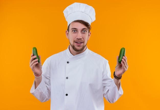 Um jovem chef barbudo, de uniforme branco, segurando pepinos verdes frescos enquanto olha para uma parede laranja