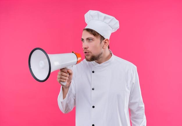 Um jovem chef barbudo de uniforme branco segurando um megafone e falando através dele em uma parede rosa