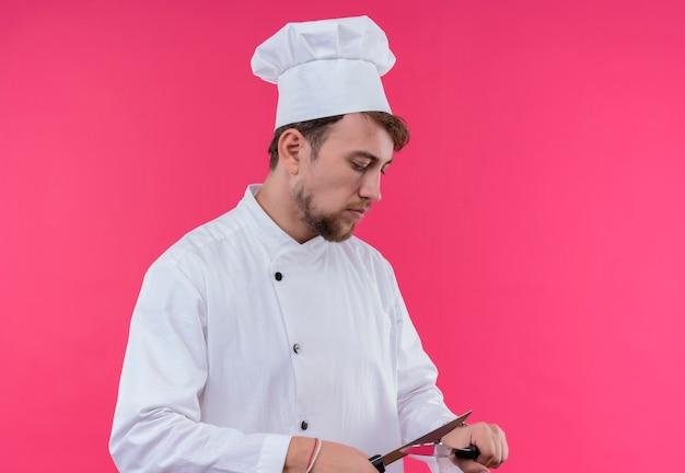 Um jovem chef barbudo em uniforme branco afiando uma faca em pé em uma parede rosa