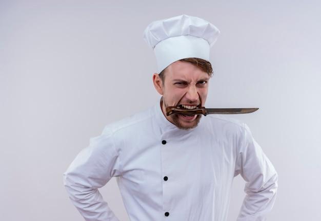 Um jovem chef barbudo furioso vestindo uniforme branco de fogão e chapéu segurando uma faca na boca enquanto olha para uma parede branca