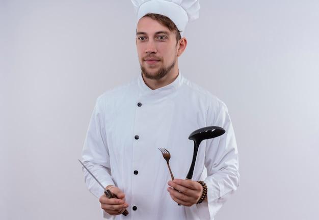 Um jovem chef barbudo pensativo vestindo uniforme branco de fogão e chapéu segurando uma faca, um garfo e uma concha enquanto olha para o lado em uma parede branca