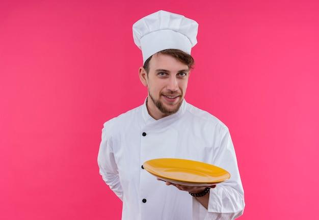 Um jovem chef barbudo positivo em uniforme branco apresentando um prato amarelo pronto para comer enquanto olha para uma parede rosa