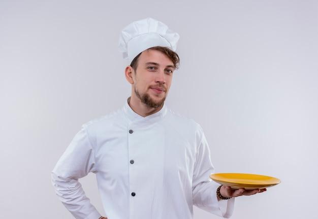 Um jovem chef barbudo satisfeito com uniforme branco apresentando um prato amarelo pronto para comer enquanto olha para uma parede branca