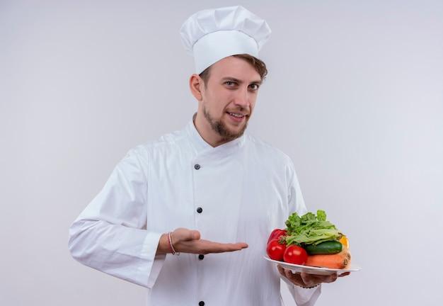 Um jovem chef barbudo satisfeito vestindo uniforme branco de fogão e chapéu mostrando um prato branco com vegetais frescos como tomates, pepinos e alface em uma parede branca