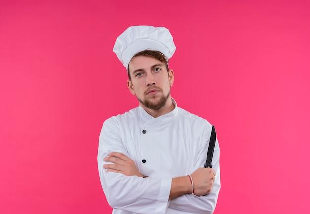 Um jovem chef barbudo sério com uniforme branco segurando uma faca enquanto olha para uma parede rosa