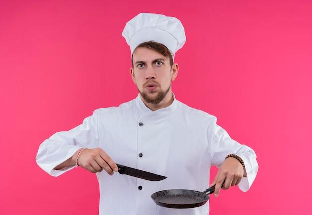 Um jovem chef barbudo sério com uniforme branco segurando uma frigideira com uma faca enquanto olha para uma parede rosa