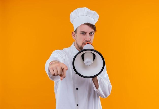Um jovem chef barbudo sério, de uniforme branco, falando através do megafone enquanto olha para uma parede laranja