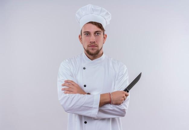 Um jovem chef barbudo sério de uniforme branco segurando uma faca enquanto olha para uma parede branca