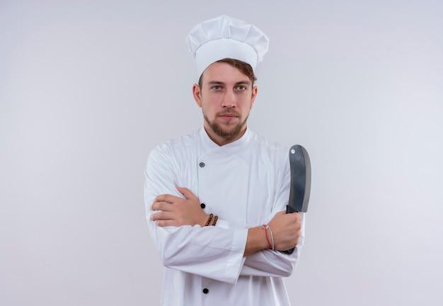 Um jovem chef barbudo sério vestindo uniforme branco de fogão e chapéu segurando cutelo enquanto olha para uma parede branca