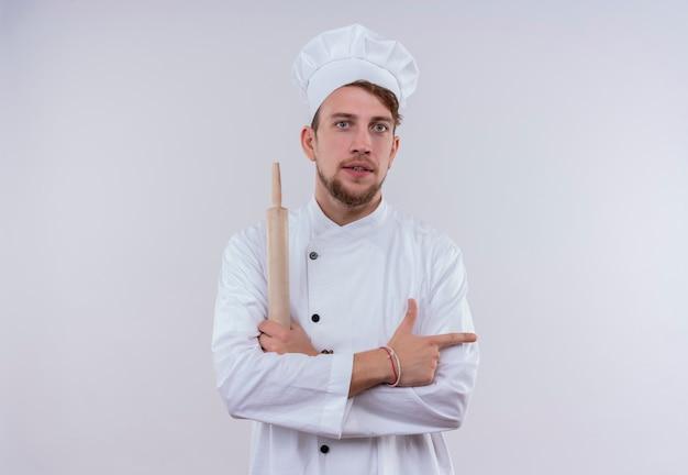 Um jovem chef barbudo sério vestindo uniforme de fogão branco e chapéu segurando o rolo de massa e apontando para o lado enquanto olha para uma parede branca