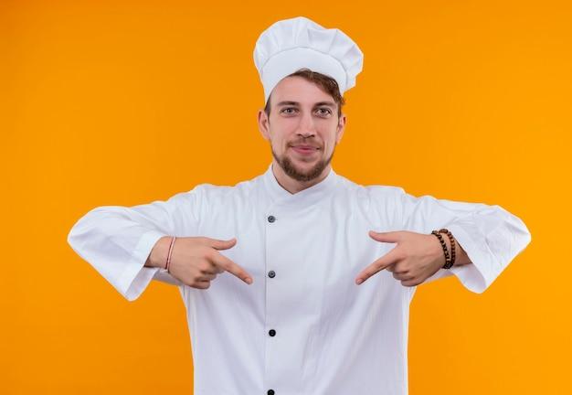 Um jovem chef barbudo sorridente com uniforme branco apontando para baixo com o dedo indicador enquanto olha para uma parede laranja