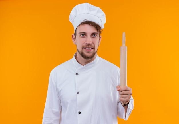 Um jovem chef barbudo sorridente de uniforme branco segurando o rolo de massa enquanto olha para uma parede laranja