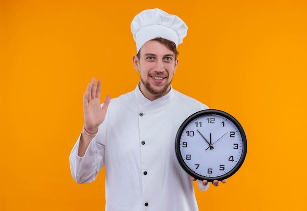 Um jovem chef barbudo sorridente de uniforme branco segurando um relógio de parede enquanto olha para uma parede laranja