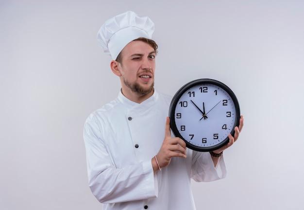 Um jovem chef barbudo vestindo uniforme branco de fogão e chapéu mostrando o relógio de parede e piscando um olho enquanto olha para uma parede branca