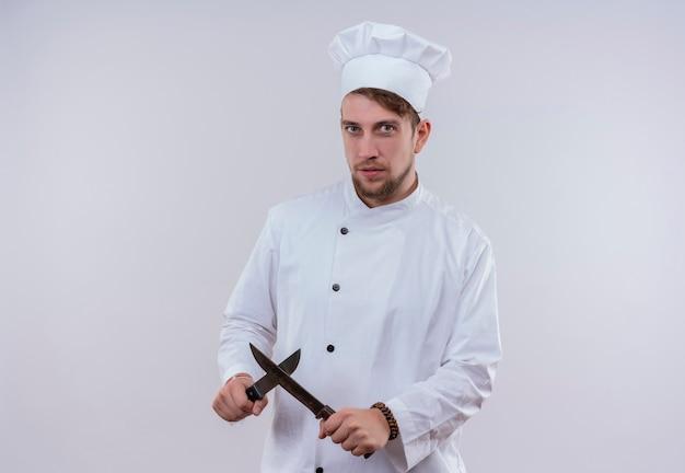 Um jovem chef barbudo vestindo uniforme branco de fogão e chapéu mostrando o sinal x com uma faca enquanto olha para uma parede branca
