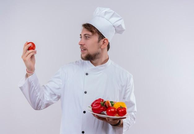 Um jovem chef barbudo vestindo uniforme branco de fogão e chapéu olhando para o tomate, enquanto segura um prato branco com vegetais frescos, como tomates, pepinos, alface em um fundo branco