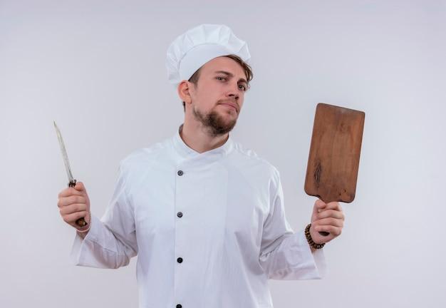 Um jovem chef barbudo vestindo uniforme branco de fogão e chapéu segurando uma placa de cozinha de madeira e uma faca enquanto olha com uma cara séria em uma parede branca
