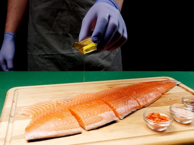 Um jovem chef derrama óleo em um filé de salmão cru fresco e temperos ficam próximos em uma tábua de madeira. conceito de comida saudável