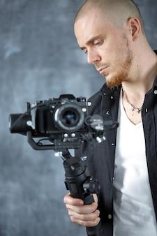 Um jovem cinegrafista profissional grava um vídeo usando a câmera em um estabilizador de cardã de 3 eixos