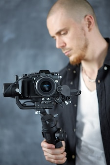 Um jovem cinegrafista profissional grava um vídeo usando uma câmera de cinema em um estabilizador de gimbal de 3 eixos
