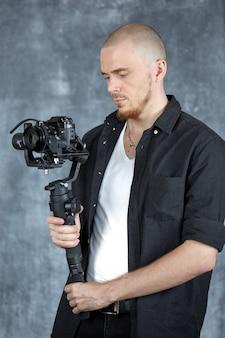 Um jovem cinegrafista profissional segura a câmera em um estabilizador de cardã de 3 eixos