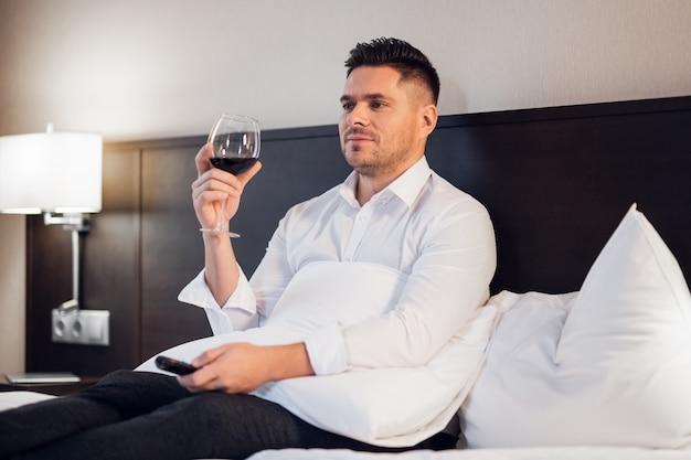 Um jovem colarinho branco, tomando uma taça de vinho em casa depois do trabalho