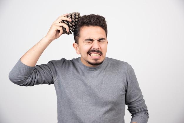 Um jovem colocando uma pinha acima da cabeça.