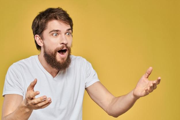 Um jovem com barba em uma camiseta mostra emoções diferentes, diversão, tristeza