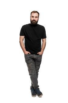 Um jovem com barba mantém as mãos nos bolsos. morena linda em uma camiseta preta e jeans cinza. altura toda. isolado em um fundo branco. vertical.