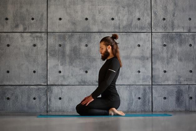 Um jovem com barba praticando ioga na academia