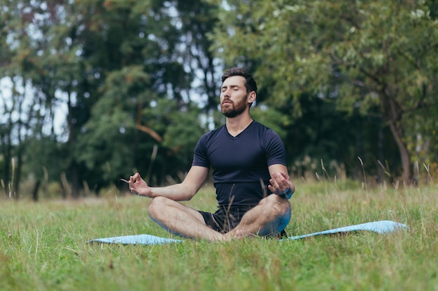 Um jovem com barba sentado no parque em uma esteira medita, realiza exercícios para melhorar a respiração, estilo de vida ativo