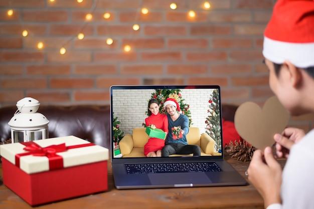 Um jovem com chapéu de papai noel vermelho fazendo videochamada na rede social com família e amigos no dia de natal.