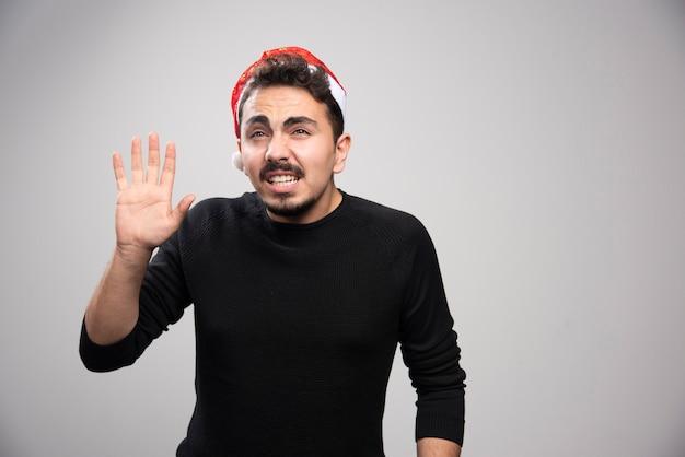 Um jovem com chapéu vermelho de papai noel acenando