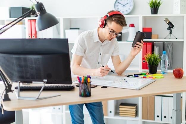 Um jovem com óculos e fones de ouvido tem um copo de café na mão e desenha um marcador na lousa.