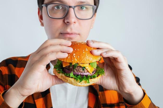 Um jovem com óculos segurando um hamburguer fresco.