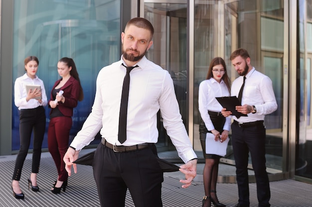 Um jovem com os bolsos acabou contra o pano de fundo do escritório