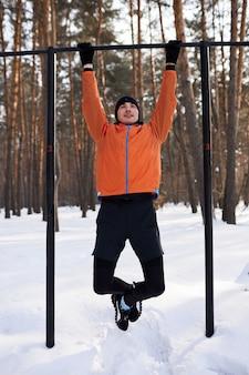 Um jovem com roupas esportivas brilhantes está se exercitando em um campo de esportes em um dia de inverno