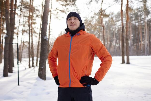 Um jovem com roupas esportivas brilhantes gosta de correr pela floresta em um dia de inverno