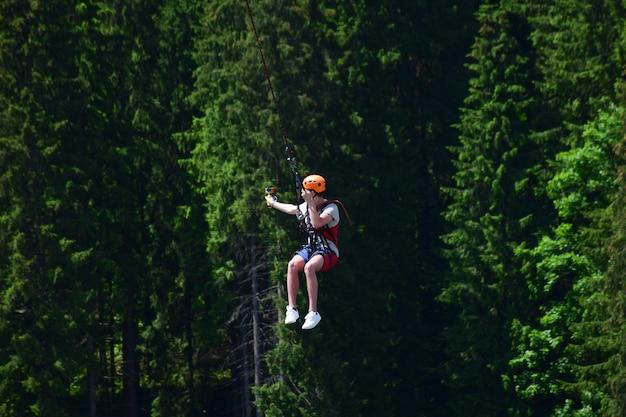 Um jovem com um capacete saltou de bungee jumping e agora se pendura em uma corda, balançando e filmando a si mesmo em uma câmera de vídeo esportiva contra um fundo desfocado de uma floresta verde